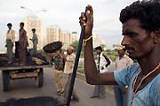 Men repairing a tarmac road in Gurgaon, India