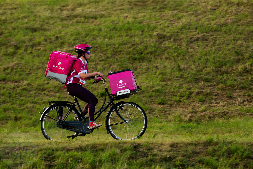 Een bezorger van Foodora rijdt op haar omafiets. In Nieuwegein wordt het NK Fietskoerieren gehouden. Fietskoeriers uit Nederland strijden om de titel door op een parcours het snelst zoveel mogelijk stempels te halen en lading weg te brengen. Daarbij moeten ze een slimme route kiezen.<br /> <br /> In Nieuwegein bike messengers battle for the Open Dutch Bicycle Messenger Championship.