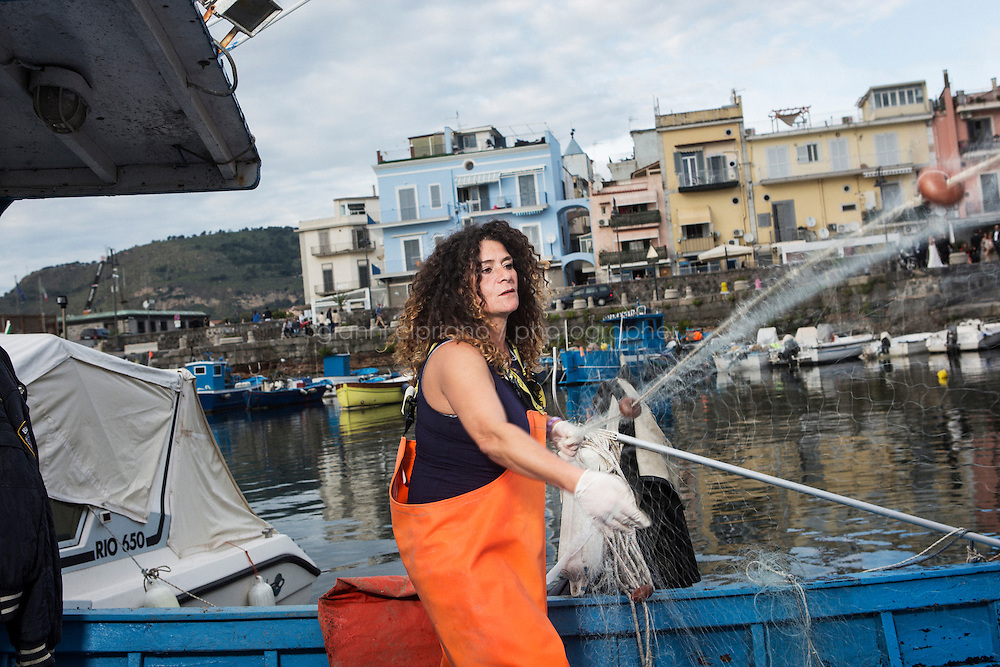 """POZZUOLI, ITALY - 8 OCTOBER 2016: Cristina Pinto (47), also known as """"Nikita"""", a former Camorra killer turned into a fisherwoman, pulls the fishing net on her boat in the port of Pozzuoli, a city of the Metropolitan area of Naples, Italy, on October 8th 2016.<br /> <br /> Cristina Pinto started her criminal career at 16 with armed robberies. By the time she turned 20 years old, she became the bodyguard of Camorra boss Mario Perrella as well as the first woman to become a killer for the criminal organization. When she was arrested in 1992, at the age of 22 years old, she was charged and sentenced for at least three homicides and for criminal conspiracy. She spent the following 22 years in prison. When released, she became a fisherwoman. She now fishes with her partner Raffaele."""