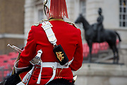 An officer with the The Queens Life Guard red tunics change guard with the Blues and Royals blue tunics during the daily ceremonial in Horse Guards Parade, on 11th June 2019, in London, England. Life Guards have stood guard at Horse Guards, the official entrance to St James and Buckingham Palace, since the Restoration of King Charles II in 1660.