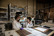 Rome, Vatican Museums, ethnological workshop (Chinese parchment, fabric and feathers). in the back from the left Stefania Passerin and Flavia Serena di Lapigioi paper art restorer. <br /> on the front deesk: Catherine Rivière painting art restorer and  Martina Brunori textil art restorer