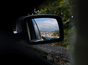 The city of San Sebastian seen through a cars wing mirror as it drives away in Spain