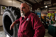 Billy Shahinian, who sells tires for large farm equipment in the Shenandoah valley, at his both inside the Farm Show. Vendors and farmers meet at The Virginia Farm Show in Fishersville, VA, Wednesday, January 17, 2018. The Farm Show is the only agricultural trade show in Virginia that caters to the full-time, as well as the part-time farmer. Photo by Justin Ide