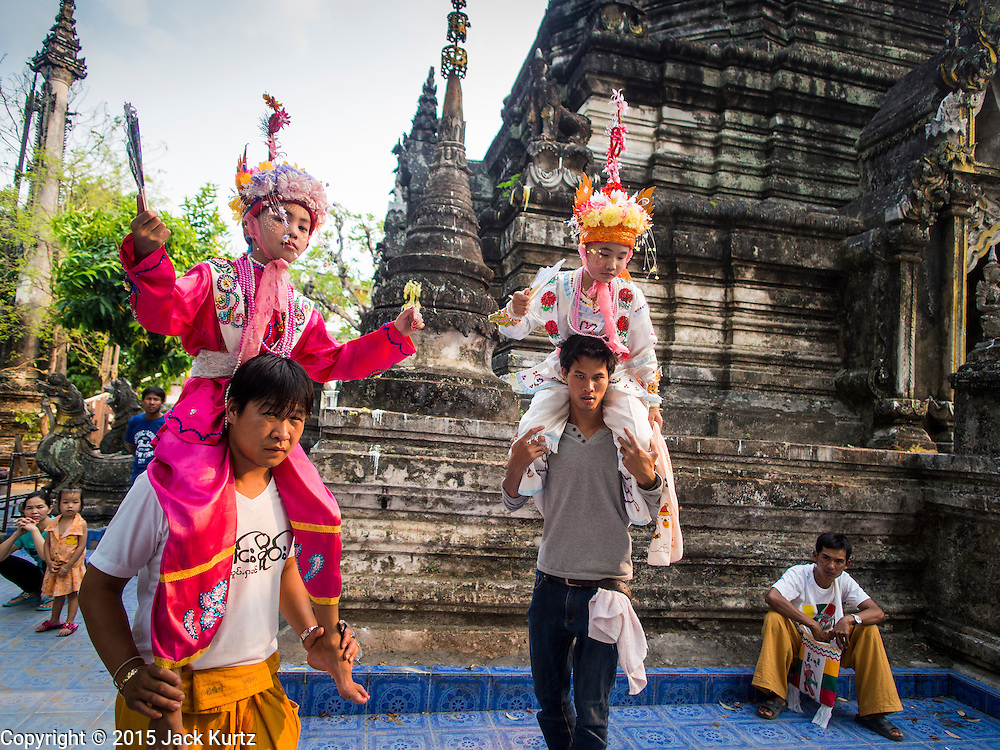 """05 APRIL 2015 - CHIANG MAI, CHIANG MAI, THAILAND:  Boys and their family member attendants in front of the chedi (stupa) on the second day of the three day long Poi Song Long Festival in Chiang Mai. The Poi Sang Long Festival (also called Poy Sang Long) is an ordination ceremony for Tai (also and commonly called Shan, though they prefer Tai) boys in the Shan State of Myanmar (Burma) and in Shan communities in western Thailand. Most Tai boys go into the monastery as novice monks at some point between the ages of seven and fourteen. This year seven boys were ordained at the Poi Sang Long ceremony at Wat Pa Pao in Chiang Mai. Poy Song Long is Tai (Shan) for """"Festival of the Jewel (or Crystal) Sons.    PHOTO BY JACK KURTZ"""
