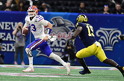 Florida Gators quarterback Feleipe Franks (13) attempts to get away from Michigan Wolverines defensive lineman Kwity Paye (19) during the Chick-fil-A Bowl Game against Michigan Wolverines at  the Mercedes-Benz Stadium, Saturday, December 29, 2018, in Atlanta. ( Kyle Hess via Abell Images for Chick-fil-A Kickoff)