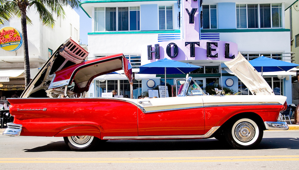A rare, 1957 Ford Skyliner hardtop convertible with its top half-folded during Art Deco Weekend, an annual January festival on Miami Beach's Ocean Drive.<br /> <br /> In the background is the streamlined, Art Deco-stye Colony Hotel, designed by Henry Hohauser in 1935.