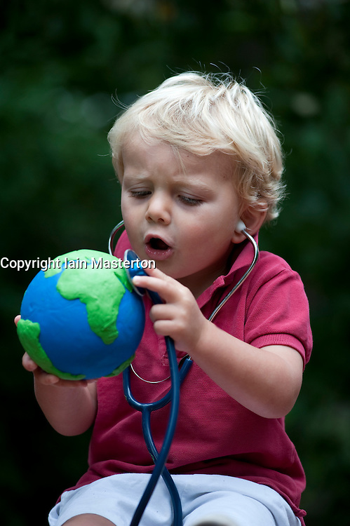 Young boy holding model of planet Earth and using a stethoscope to chek its health