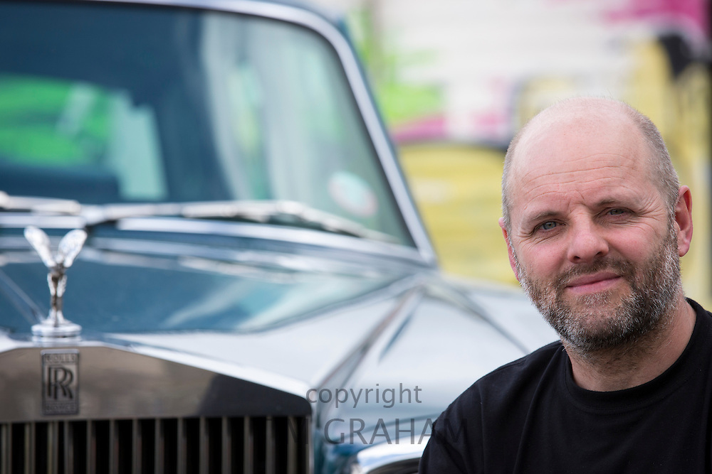 Gavin Turk, artist, photographed with his old Rolls Royce car near his East London studio, United Kingdom