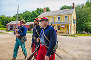 """Old Bethpage, New York, USA. 30th August, 2015. At center, Andrew Preble from Long Beach portrays an American Civil War Captain from the 14th Brooklyn Regiment (14th New York State Militia) AKA The Brooklyn Chasseurs, in front of the yellow and white Noon Inn during the Old Time Music Weekend at the Old Bethpage Village Restoration. During their historical reenactments, members of the non-profit 14th Brooklyn Company E wear reproductions of """"The """"Red Legged Devils"""" original Union army uniform."""