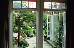 Looking out through the dining room window to patio and garden beyond. Shows the coloured glass which inspired the circular design theme.