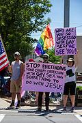 Demonstrators hold signs at the Mifflinburg Pride Event .