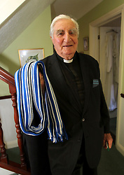 "© Licensed to London News Pictures. 01/02/2012. Uckfield, UK. BILL PETERS at home holding a scarf for the team Brighton and Hove Albion fro whom he played before WWII. Canon Bill Peters of Uckfield, the only chaplain who served in the Second World War still working, is celebrating his 70th year in the church as he approaches his 93rd birthday this year. It has been 67 years since he signed up with the Royal Army Chaplains Department. Canon Peters, who lives in Uckfield is a widower of 10 years and a grand-father of two, He claims he still has a lot left to achieve and said: ""If anybody wants to get married, and the parish is happy, then I do them. I do more weddings than funerals. I have been a priest for 70 years this year and I have spent all that time in Sussex, except when I was in the army and canon of a cathedral."" Photo credit : Ron Hill/LNP NOTE TO EDITORS - WORDS AVAILABLE HERE: http://tinyurl.com/73zbhmu"