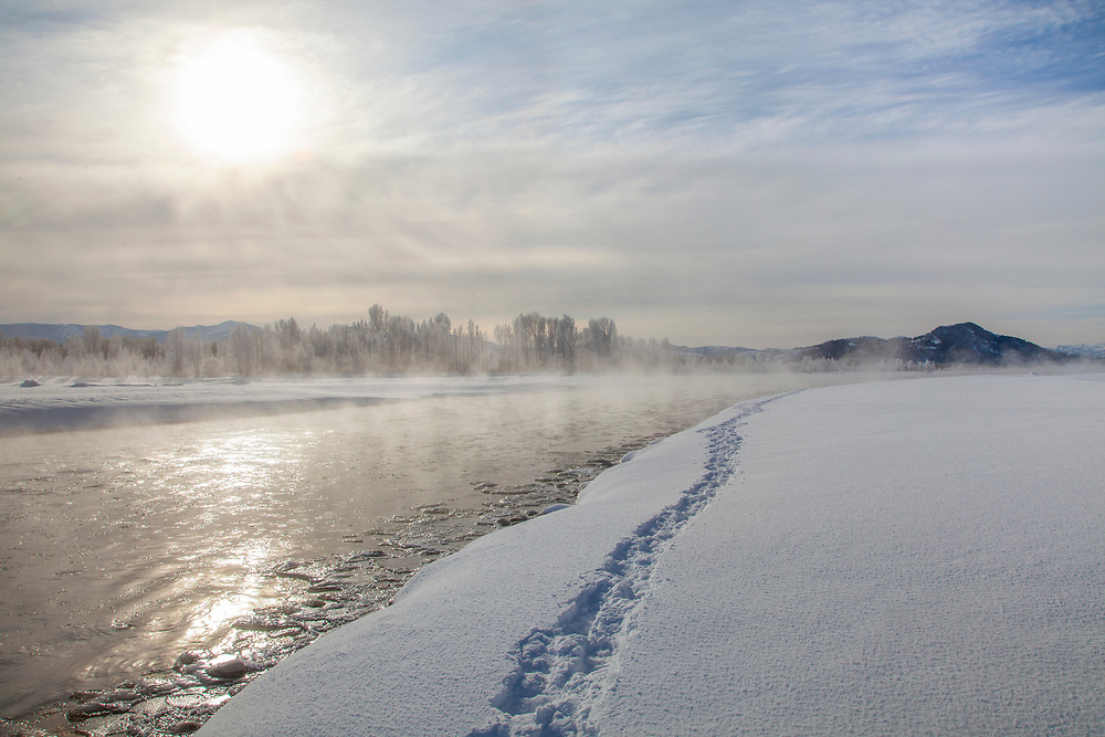 Sub zero temperatures create ice flows on the Snake River near Teton Village in Wyoming with foot prints along rivers edge on a winter morning.  Licensing and Open Edition Prints.