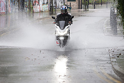 © Licensed to London News Pictures.  28/07/2021. London, UK. A man is caught during a torrential downpour in Hackney, east London. According to The Met Office, wet weather is expected in the capital for this week. Photo credit: Marcin Nowak/LNP