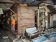 21 SEPTEMBER 2015 - BANGKOK, THAILAND: A demolition worker stands in the doorway of a home being torn down near Wat Kalayanamit. Fiftyfour homes around Wat Kalayanamit, a historic Buddhist temple on the Chao Phraya River in the Thonburi section of Bangkok are being razed and the residents evicted to make way for new development at the temple. The abbot of the temple said he was evicting the residents, who have lived on the temple grounds for generations, because their homes are unsafe and because he wants to improve the temple grounds. The evictions are a part of a Bangkok trend, especially along the Chao Phraya River and BTS light rail lines. Low income people are being evicted from their long time homes to make way for urban renewal.    PHOTO BY JACK KURTZ