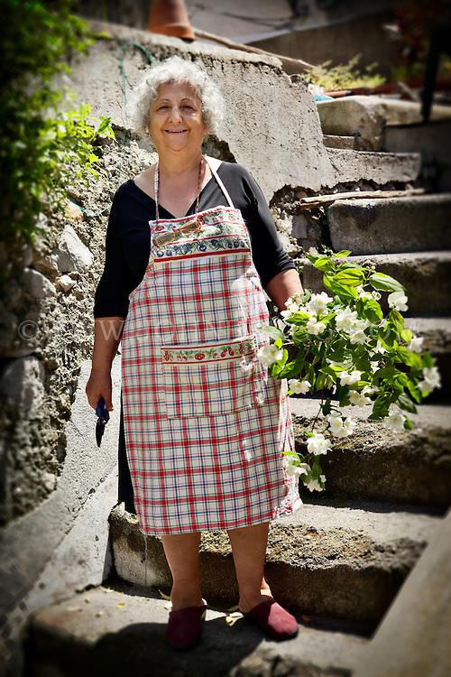 Elderly Italian woman in a garden with flowers, Amalfi, Italy.