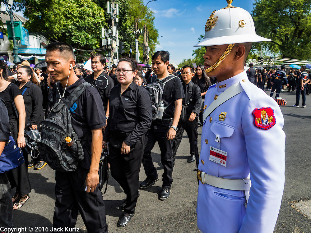22 OCTOBER 2016 - BANGKOK, THAILAND: Mourners walk past a member of the honor guard and go into the Grand Palace Saturday. Sanam Luang, the Royal Ceremonial Ground, was packed Saturday with more than 100,000 people mourning the Monarch's death. The King died Oct. 13, 2016. He was 88. His death came after a period of failing health. Bhumibol Adulyadej was born in Cambridge, MA, on 5 December 1927. He was the ninth monarch of Thailand from the Chakri Dynasty and is also known as Rama IX. He became King on June 9, 1946 and served as King of Thailand for 70 years, 126 days. He was, at the time of his death, the world's longest-serving head of state and the longest-reigning monarch in Thai history.       PHOTO BY JACK KURTZ