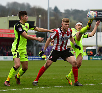 Lincoln City's Elliott Whitehouse vies for possession with Exeter City's Jordan Storey, left, and Exeter City's Jordan Tillson<br /> <br /> Photographer Chris Vaughan/CameraSport<br /> <br /> The EFL Sky Bet League Two - Lincoln City v Exeter City - Friday 30th March 2018 - Sincil Bank - Lincoln<br /> <br /> World Copyright © 2018 CameraSport. All rights reserved. 43 Linden Ave. Countesthorpe. Leicester. England. LE8 5PG - Tel: +44 (0) 116 277 4147 - admin@camerasport.com - www.camerasport.com