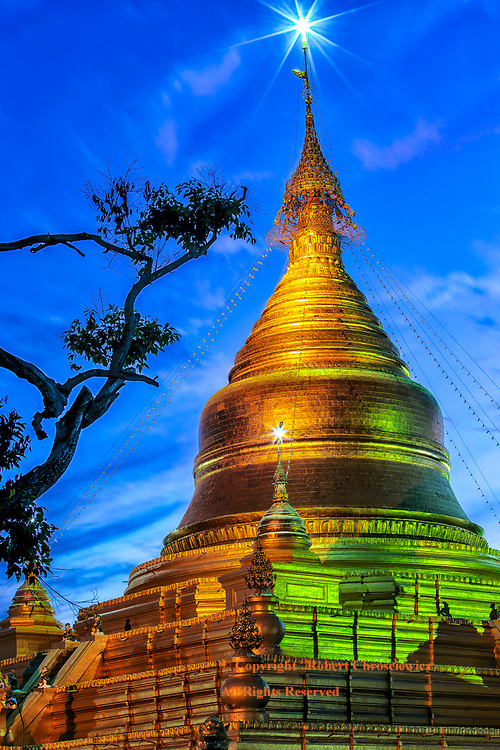 Kuthodaw Pagoda is cast in a golden light at sunset, while a trees branch reaches out and mimics the outline of the stupa,  Mandalay Myanmar.