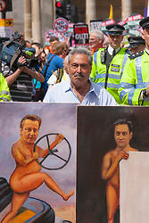 London, June 21st 2014. Artist Kaya Mar displays his latest satirical painting showing Cameron having lost control and Milliband having no visible policies.