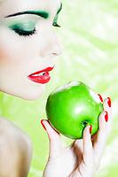 beautiful caucasian woman portrait eating an apple studio on green background
