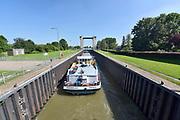 Nederland, Heerewaarden, 6-6-2018  Een binnenvaartschip vaart de sluis in om geschut te worden van de Maas naar de Waal . Via het kanaal van Sint Andries en de Sint Andriessluis . De Waal is het Nederlandse deel van de Rijn en de belangrijkste vaarroute van en naar Rotterdam en Duitsland . Aftakkingen zijn de minder bevaren Neder Rijn en IJssel.Foto: Flip Franssen