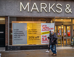 © Licensed to London News Pictures. 22/02/2021. London, UK. Shoppers walk past discount sales signs at M&S on Richmond Town Centre in South West London today. Prime Minister Boris Jonson has announced in the Commons this afternoon his plan for unlocking the UK and the gradual easing of Covid-19 restrictions with shops and pubs to open by April 12th and schools back by 8th March with every adult vaccinated by the end of July. Photo credit: Alex Lentati/LNP