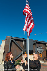 HOG Magazine editor Matt King and HD District Rep Leah Whaley raise a flag at the Harley-Davidson rally point for the kickoff of the USS South Dakota submarine flag relay across South Dakota. Sturgis, SD. USA. Saturday October 7, 2017. Photography ©2017 Michael Lichter.