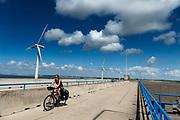 Fietsers rijden over de Haringvlietdam bij Rockanje. De Haringvlietdam is een waterkering tussen de Noordzee en de Haringvliet en is onderdeel van de Deltawerken waarmee Nederland beschermt wordt tegen overstromingen bij springvloed.  <br /> <br /> Cyclists pass the Haringvlietdam near Rockanje. The Haringvlietdam is a flood defense system and is part of the Delta Works that protects the Netherlands against flooding in the event of a flood.