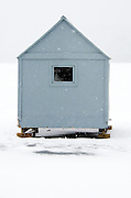 A small blue ice fishing shack in a snowstorm.