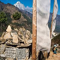 A woman carries loads past A tibetan Buddhist mani wal & prayer flags in the Khumbu region of Nepal 1986.