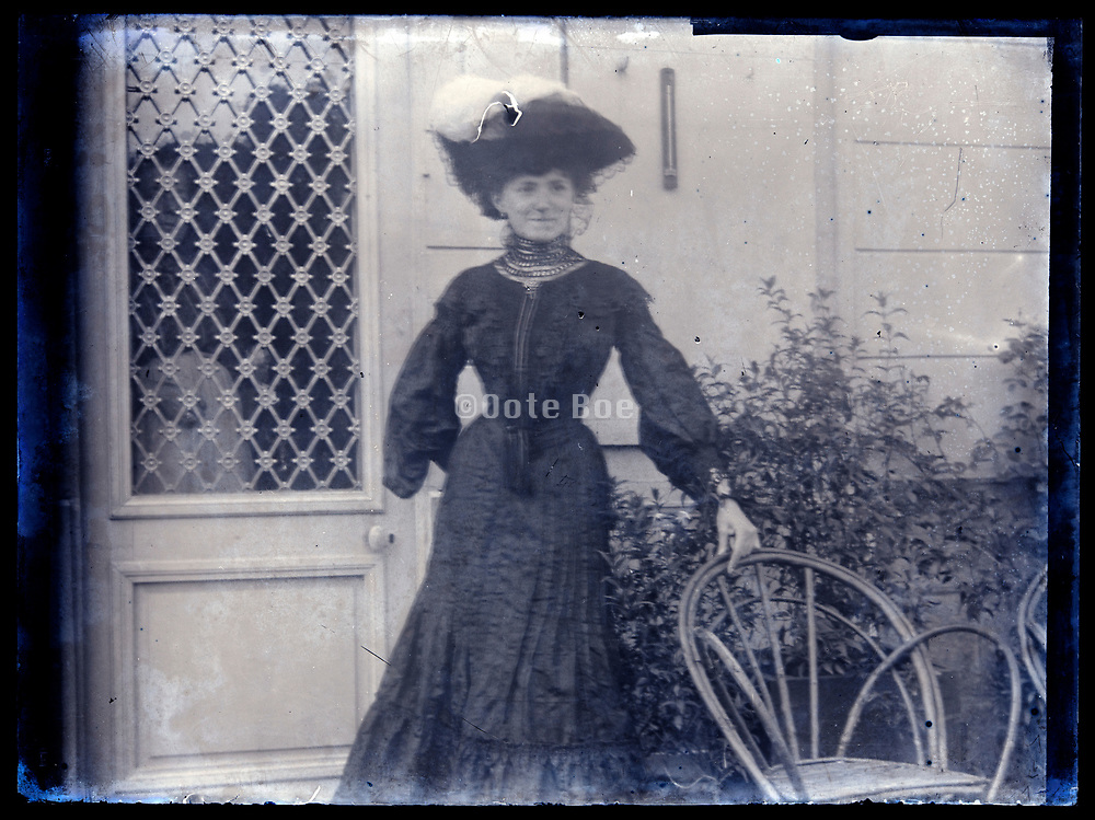 woman posing with person visible through door window standing inside France circa 1920s