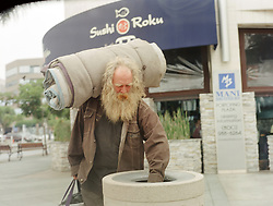 homeless man with hand in garbage can in Los Angeles, CA