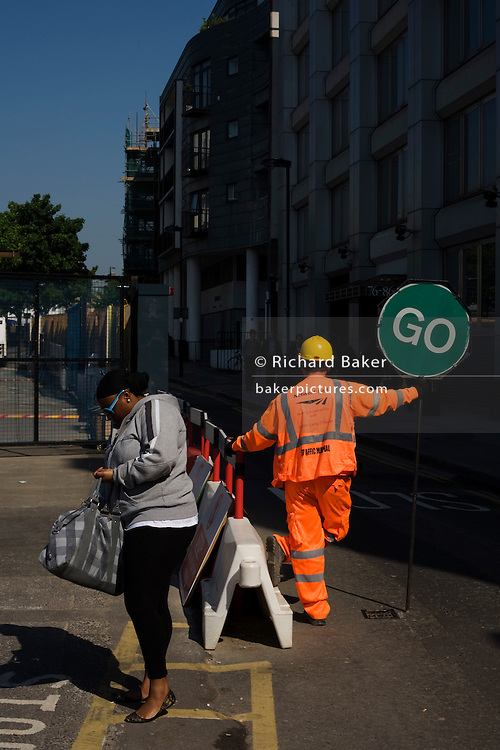 A Stop / Go banksman dressed in a high-vis suit stands on a public road for oncoming traffic as a pedestrian pauses in street.