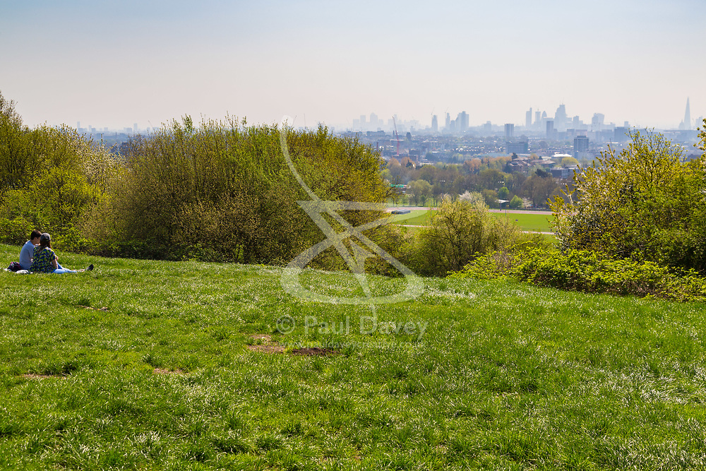 Two people enjoy the sunshine and the hazy view if the city skyline from Parliament Hill in London February 10 2018.