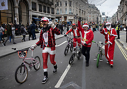 © Licensed to London News Pictures. 12/12/2020. London, UK. Cyclists dressed as Santa Claus make their way along Regent Street, has been pedestrianised for the day. Experts are warning that London should be placed in tier three now to avoid a rise is coronavirus deaths over the Christmas period. Photo credit: Peter Macdiarmid/LNP