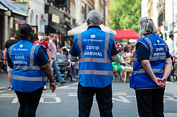 © Licensed to London News Pictures. 12/06/2021. LONDON, UK. City of Westminster Covid Marshals on patrol in Soho.  Scientific advisers to the UK government have called for a delay to the complete lifting of coronavirus lockdown restrictions on 21 June, possibly by four weeks, to allow scientists to assess the link between rising numbers of Covid-19 cases (mainly the newly identified Delta variant) and hospital admissions.  Photo credit: Stephen Chung/LNP