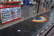 As the government announces the move from Tier 2 to Tier 3 before Christmas, a few shoppers walk towards a rainbow on the widened pavement, enlarged to ensure social distancing during the second wave of the Coronavirus pandemic, on 14th December 2020, in London, England.