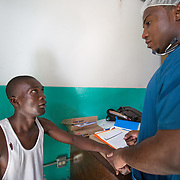 CAPTION: Emmanuel, who has already undergone cleft repair surgery in the past, has come for consultation. His lip retracted after the operation, so he now needs a revision. LOCATION: Hôpital Universitaire Justinien, Cap-Haïtien, Haiti. INDIVIDUAL(S) PHOTOGRAPHED: Emmanuel Fenélus (left) and Stanley Loriston (right).