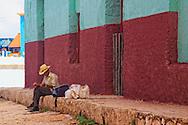 Man sitting on the sidewalk in Gibara, Holguin, Cuba.