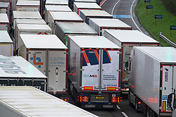 © Licensed to London News Pictures. 12/12/2020. <br /> Folkestone, UK. Freight lorries queue at the Channel Tunnel in Folkestone. Hundreds of lorries continue to queue for a fifth day at the Port of Dover the Channel Tunnel and on the M20 this Saturday afternoon in Kent.The high volume of freight traffic is attributed to the pre-Christmas rush, stockpiling and Coronavirus vaccine delivery. Photo credit:Grant Falvey/LNP