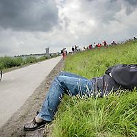 Nederland.Almere Haven.27 augustus 2005.<br /> Triathlon atleet fietst over het parcours tijdens het onderdeel 40 km wielrennen langs het IJsselmeer.Sommige bezoekers genoten van het zonnetje en vielen in slaap.<br /> Sport.Sportief.Wielrennen.Conditie.Luieren.Slapen.Genieten.Zonnen.Dijk.<br /> Participants in the Holland Triathlon 2005.