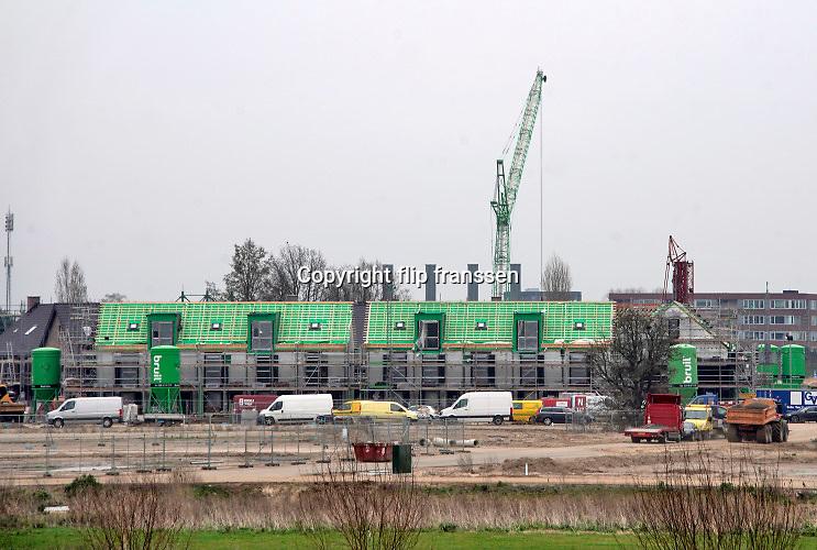 Nederland, Oosterhout, 6-3-2020  Aan de voet van de dijk in dit dorp bij Nijmegen in Gelderland worden een aantal nieuwe huizen gebouwd in de vrije huursector en als koophuis. Hogewei wordt gebouwd door de Klokgroep . Foto: Flip Franssen