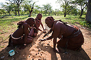 Traditionally dressed Himba girls play a game outside their home in Okapembambu village in northwestern Namibia.