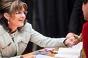 """23 NOVEMBER 2010 - PHOENIX, AZ:  SARAH PALIN looks at customer's jewelry at her book signing event in Phoenix Tuesday. Palin signed copies of her new book, """"America by Heart"""" at the store in north Phoenix Tuesday night, Nov. 23. It was the kick off of her book tour to support America by Heart. Palin is frequently mentioned as a possible Republican candidate for US President in 2012.   Photo by Jack Kurtz"""