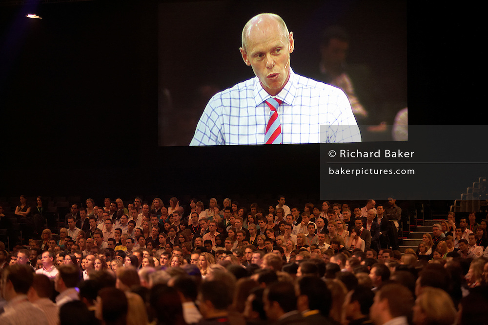 An executive peers down on his employees on a giant screen, addressing his loyal audience of his staff who have congregated at an Academy Day held for 3,000 of company London employees at Excel in London's Docklands, England. The hall is packed and his disciples listen and watch intently and obediently to watch their Leader speak like a Big Brother character, who ernestly and sincerely talks down to them despite being dressed casually for such a large event. Each employee will attend this brainstorming fair where later, motivational pep-talks from executives, outside speakers and gurus will talk to large groups of personnel so their presence on this day away from the office is vital for the year's business ahead.