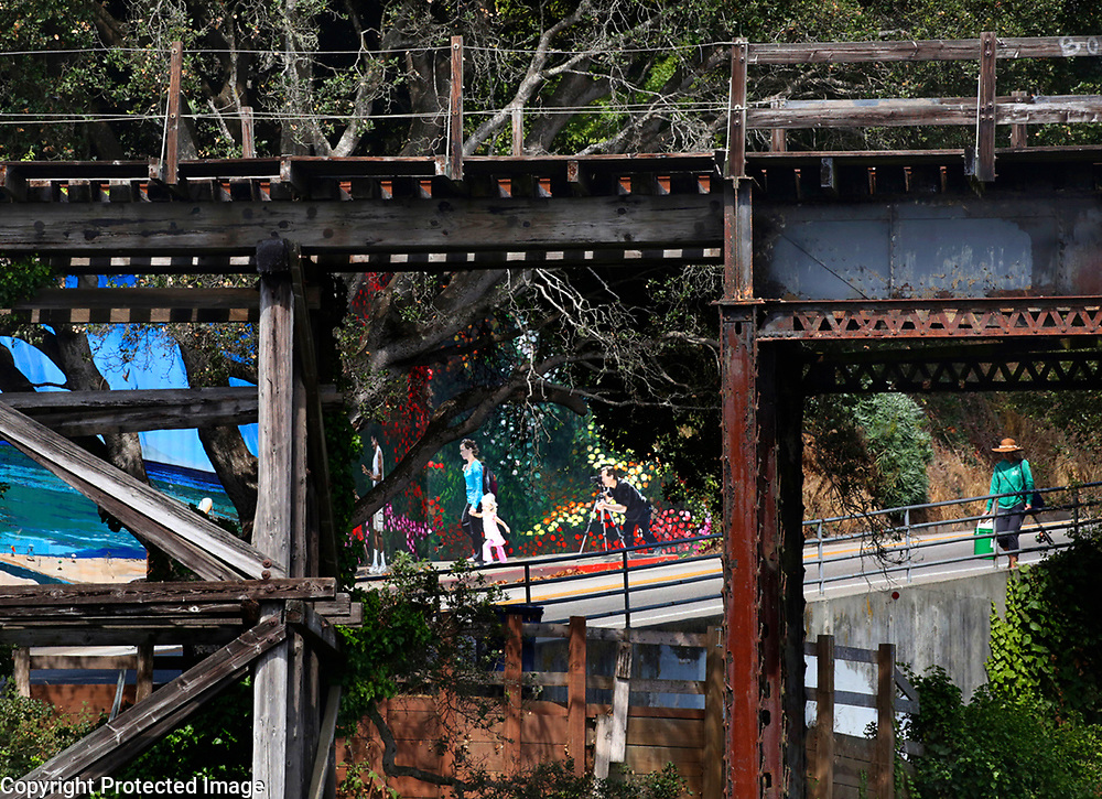 An angler makes his way along Capitola Road to the Capitola Wharf as the trestle rises above. The current trestle, constructed in the 1886, last hosted passenger railroad traffic in 1950 . Photo by Shmuel Thaler <br /> shmuel_thaler@yahoo.com www.shmuelthaler.com