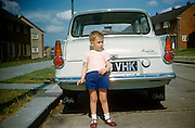 A young boy poses proudly at the rear of the family Anglia car on an Essex estate in the early nineteen sixties.
