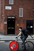 Covent Garden in the West End of London. Man on a bicycle passing the rear stage door entrance to the Cambridge Theatre on Shelton Street