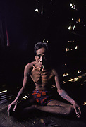 A portrait of a tattooed Kayan man, sitting cross-legged in his traditional longhouse, located on the Metah River, 14th March 1982, in Sarawak, East Malayasia Borneo. The population of the Kayan ethnic group may be around 27,000. They are part of a larger grouping of people, settled mainly along the middle reaches of the Baram, Bintulu, and Rajang rivers in Sarawak, Malaysia and referred collectively as the Orang Ulu, or upriver people. Like some other Dayak people, they are known for being fierce warriors, former headhunters, adept in Upland rice cultivation, and having extensive tattoos and stretched earlobes amongst both sexes.